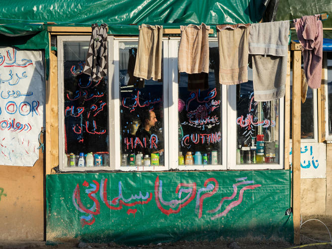 <p>A self-made barber shop with the towels drying in the main street of the Jungle in the north part of the camp. The haircuts cost around five euros.</p>