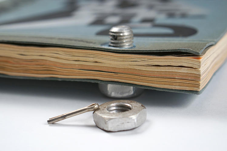 <p>The book is bound together with nuts and bolts at its spine.</p>